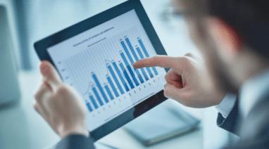 Homem analisando gráficos de orçamento de obras online em tela de tablet