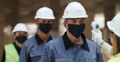 trabalhadores da construção civil com máscaras no rosto em prevenção a pandemia