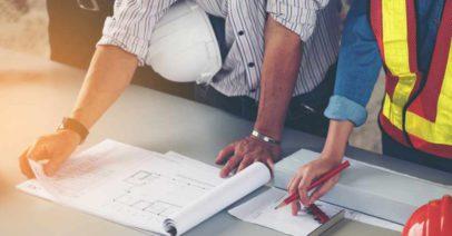 mãos masculinas e femininas sobre projeto de planejamento de obras na mesa