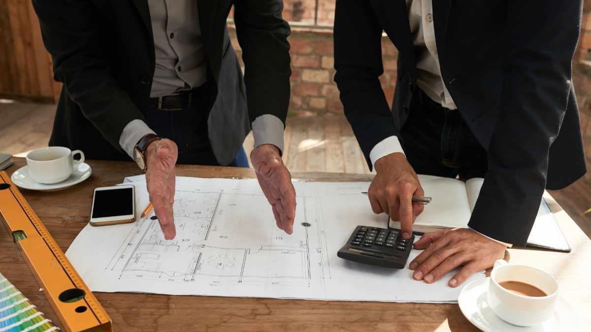 mãos masculinas sob papéis e calculadora para ilustrar orçamento de obras