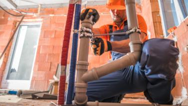 encanador agachado manuseando a instalação de canos de projeto hidrossanitário