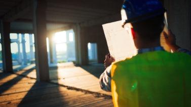 Apontador de obras usando colete e capacete com papéis nas mãos em vistoria no canteiro de obras
