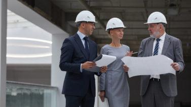 Equipe composta por dois homens e mulher analisam documento de gerenciamento de obras
