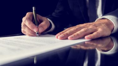 Mãos masculinas assinando documento de memorial descritivo de obras