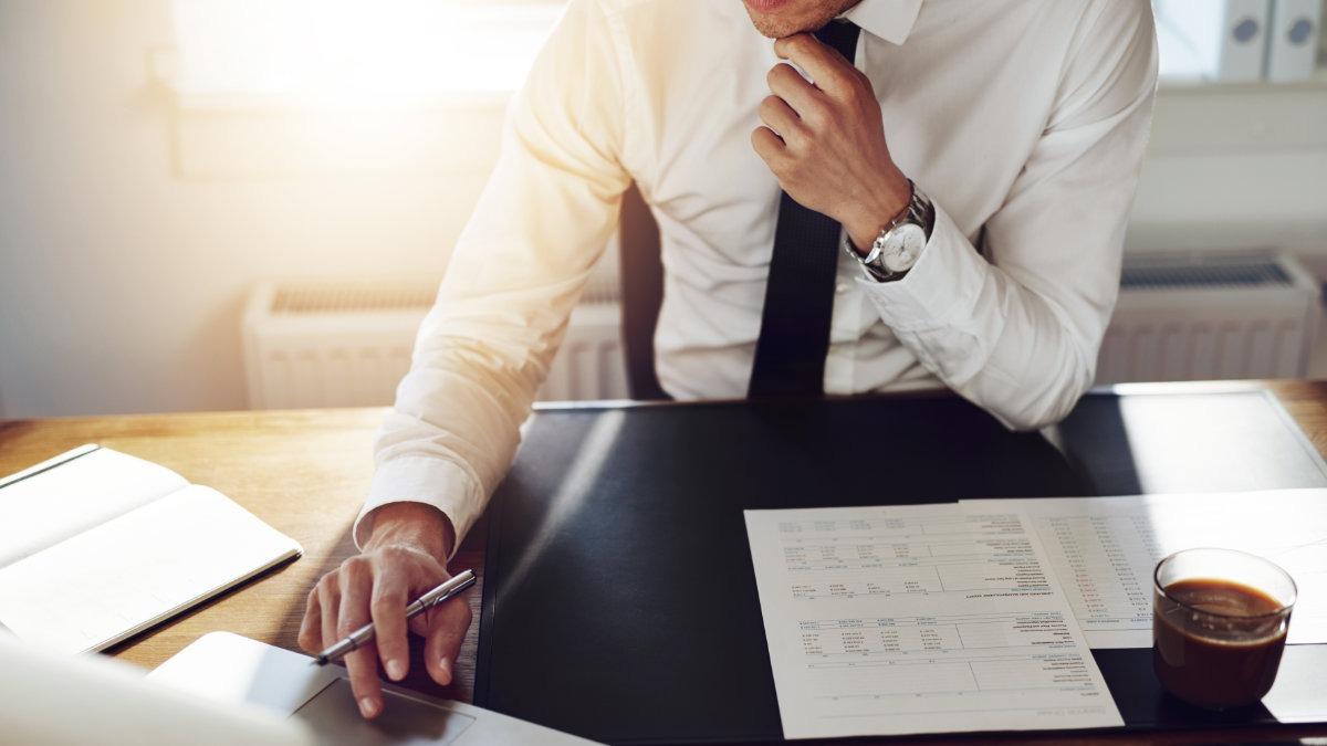 homem de camisa branca e gravata preta sentado à mesa com papéis mexe em notebook para preencher planilha para orçamento de obras